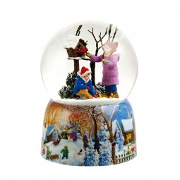 Snow globe children at a bird house with a cardinal