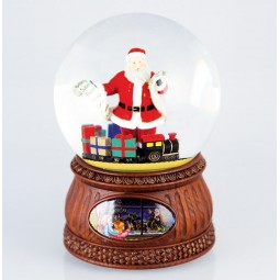 Santa with a wishing list and gifts in a snow globe